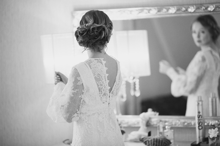 Bride getting ready while looking into mirror in hotel room. Wedding picture in black and white.