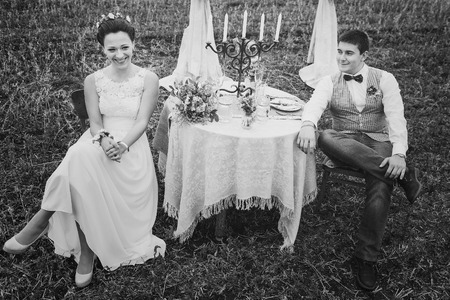 chear: Groom and bride happy together sitting near decorated wedding table.