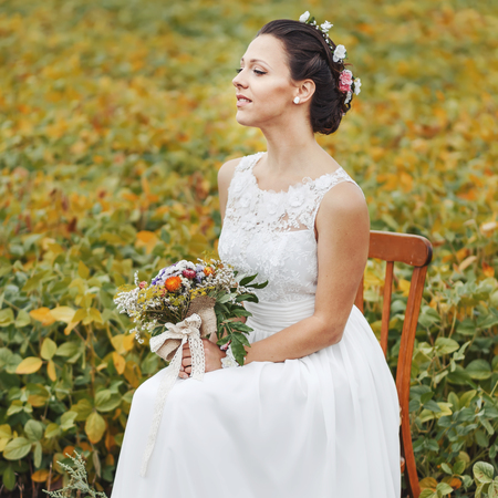 chear: Bride sitting on chair with wedding bouquet at field. Newlywed at countryside. Stock Photo