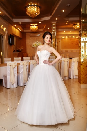 Young brunette bride wearing gorgeous wedding dress while standing in restaurant prepared for wedding.