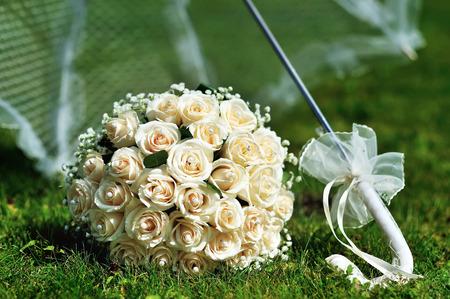 Wedding bouquet on grass under bridal fashion umbrella