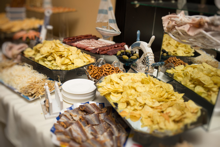Catering banquet table with baked food snacks, sandwiches, cakes, cups and plates, self serve, open buffet dinner Stock Photo