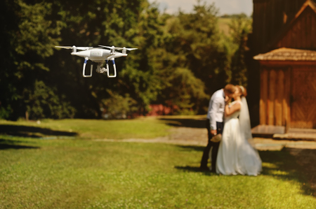 dron filming a wedding couple by the oold wooden church