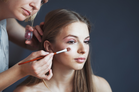 make up applying: attractive young woman having make up applying by artist in studio