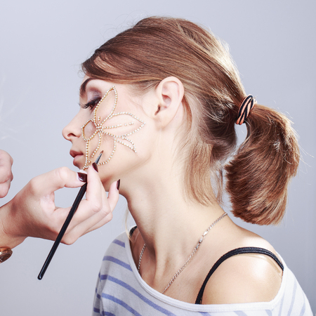 make up applying: young woman having make up applying by artist in studio