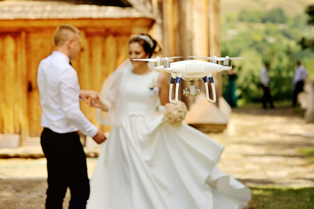 drone filming a wedding couple by the oold wooden church 免版税图像 - 70861533