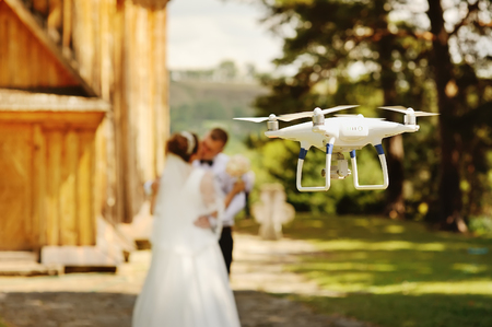 dron filming a wedding couple by the oold wooden church 免版税图像 - 70969124