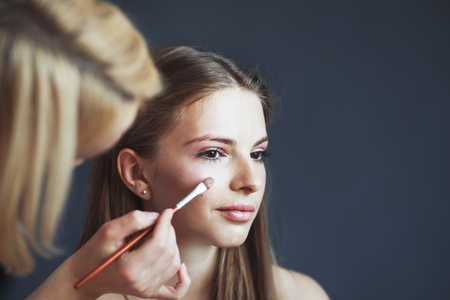attractive young woman having make up applying by artist in studio