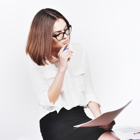 Portrait of beautiful young secretary woman working with papers at office desk. Indoors
