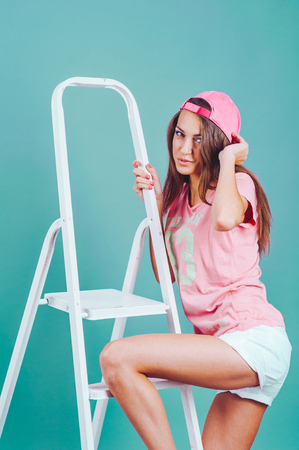 young woman sitting on a stepladder in studio