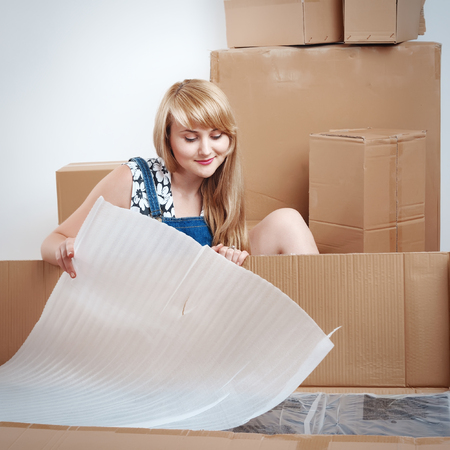 young blond woman moving into new apartment, unpacked furniture Stock Photo
