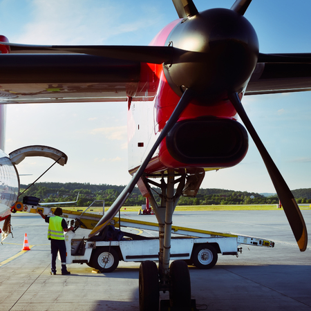 Ground crew load baggage to airplane. Aircraft is preparing for taking off.