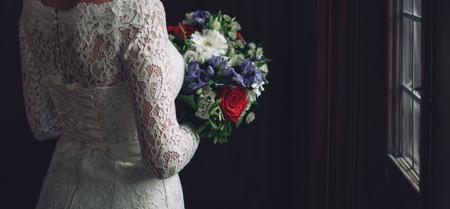 beautiful bride in stylish wedding dress holding a bouquet 免版税图像