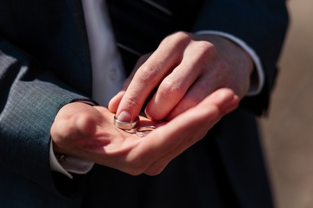 Groom holding wedding rings, waits for his bride