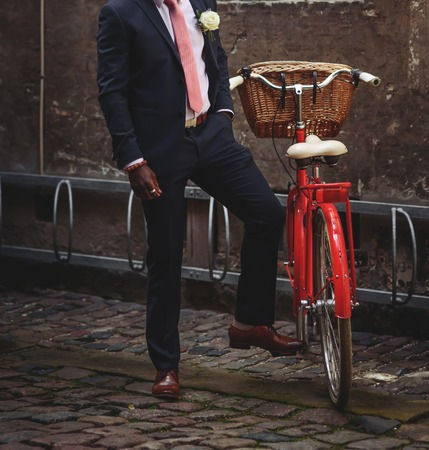 Stylish groom and red bicycle with the basket 免版税图像