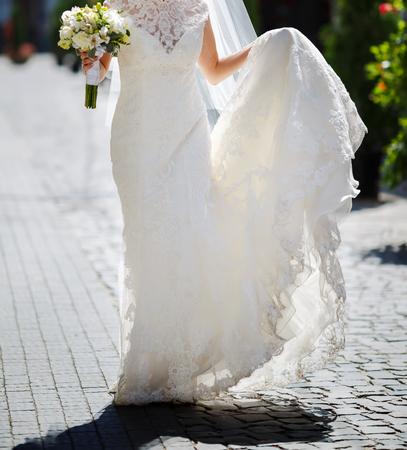 beautiful bride in stylish wedding dress holding a