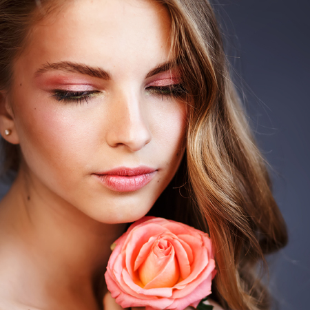 Adorable pink lips of young woman with rose in hand. 写真素材