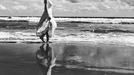 Bride walking by the sea wearing stylish classic wedding dress.