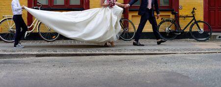 Bride walking a street wearing long classic wedding dress. 스톡 콘텐츠
