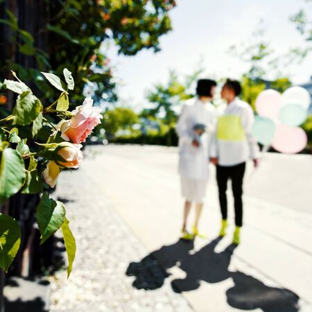 Bridal couple walking in a city with a bouquet and balloons, happy bride and groom together. 스톡 콘텐츠