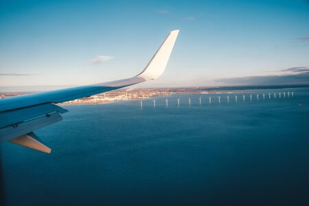 The plane approaching Copenhagen airport flying over sea full of windmill turbines.