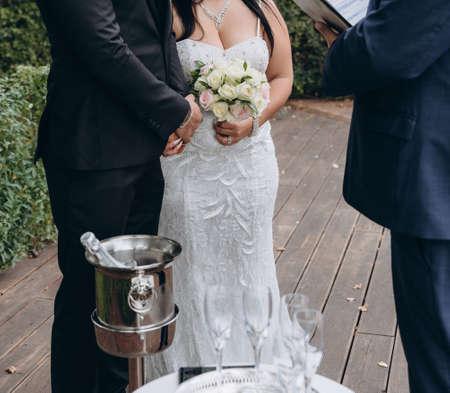Bridal couple having their official wedding ceremony next to a registrar.