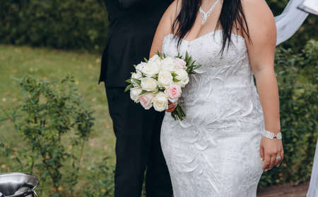 Bridal couple kissing, young bride wears white dress and holds wedding bouquet of roses.