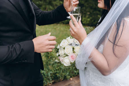 Bridal couple kissing and having champagne during wedding ceremony.