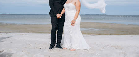 Wedding couple dancing at the beach, young bride wears white dress and long veil. Reklamní fotografie