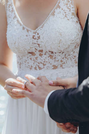 Beautiful bridal couple putting the wedding rings on.