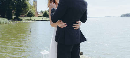 Bridal couple embracing on a pier next to a lake.