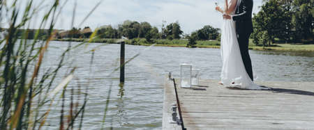Bridal couple embracing on a pier next to a lake, holding glasses with champagne. Reklamní fotografie