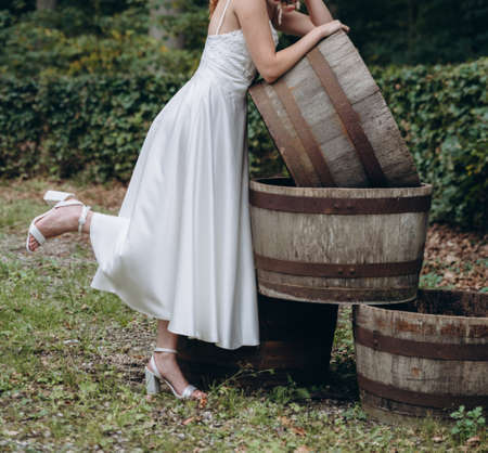 Bride in white dress holds wedding bouquet with pink tiny roses and leans on wooden barrel.