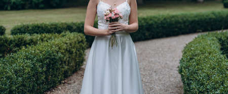 Bride in white dress holds wedding bouquet with pink tiny roses and posing.