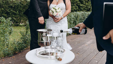 Wedding registrar fill glasses with champagne for happy bridal couple.