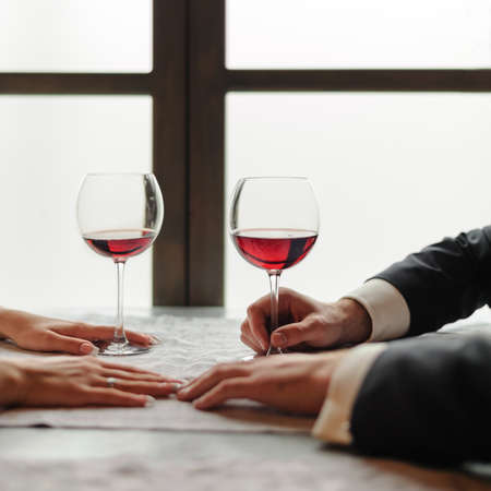The hands of a young couple who are now on a date in a restaurant, there are two glasses of red wine on the table. Valentine day and togetherness concept.