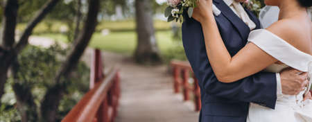 The bridal couple embrace on a small wooden red bridge, the bride is dressed in a classic wedding dress and the groom in a dark blue suit.