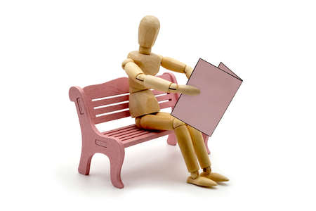 MANIKIN ON A PINK PARK BENCH WITH EMPTY PINK JOURNAL. USABLE FOR BOOK, PARK, NEWSPAPER, PUBLISHING, JOURNALISM, PRESS AND NEWS IN GENERAL.