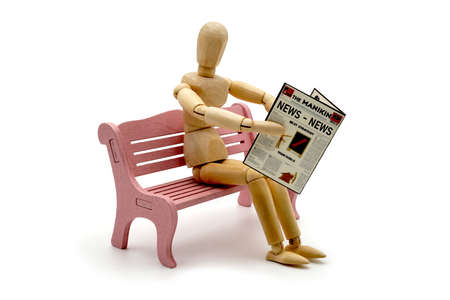 MANIKIN ON BENCH WITH NEWSPAPER AND NEWS TITLE. USABLE FOR PARK, NEWSPAPER, PUBLISHING, JOURNALISM, PRESS AND NEWS IN GENERAL.