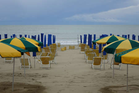 THE END OF THE SUMMER. SHORE WITH UMBRELLAS AND DECK CHAIR ON THE BEACH.