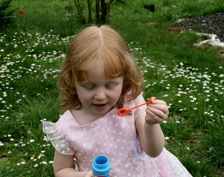 Cute girl having fun blowing bubbles outside Stock Photo