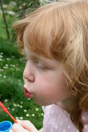 Cute girl blowing bubbles outside