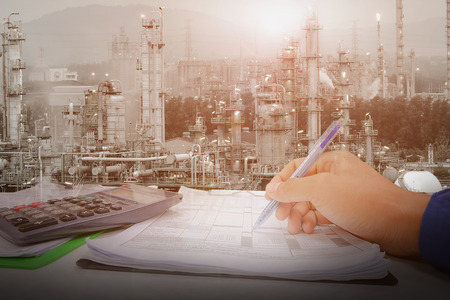 Hand holding pen for check list on paper page, Inspection and operation in control room concept, Operation petrochemical plant with control room concept