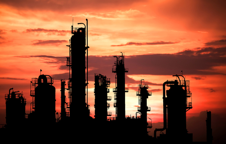 Silhouette image of distillation tower in petrochemical plant on sky sunset  background