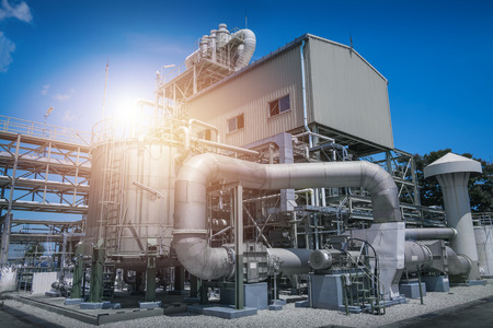 Manufacturing of industrial plant with equipment and pipeline on blue sky background