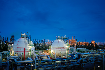 Gas storage sphere tanks and pipeline in oil and gas refinery industrial plant on blue sky twilight background Redactioneel