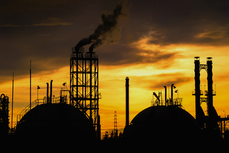 Gas storage sphere tanks and smoke stacks in silhouette image on sunset sky background