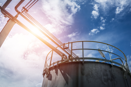 Chemical tank and pipeline on blue sky sunlight background with copy space