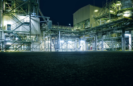 Area of manufacturing petrochemical industrial plant at night with copy space pavement floor