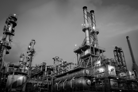 Industrial furnace and heat exchanger is cracking hydrocarbons in factory with monotone, Close up of equipment in petrochemical plant on sky background with smoke stacks Redactioneel